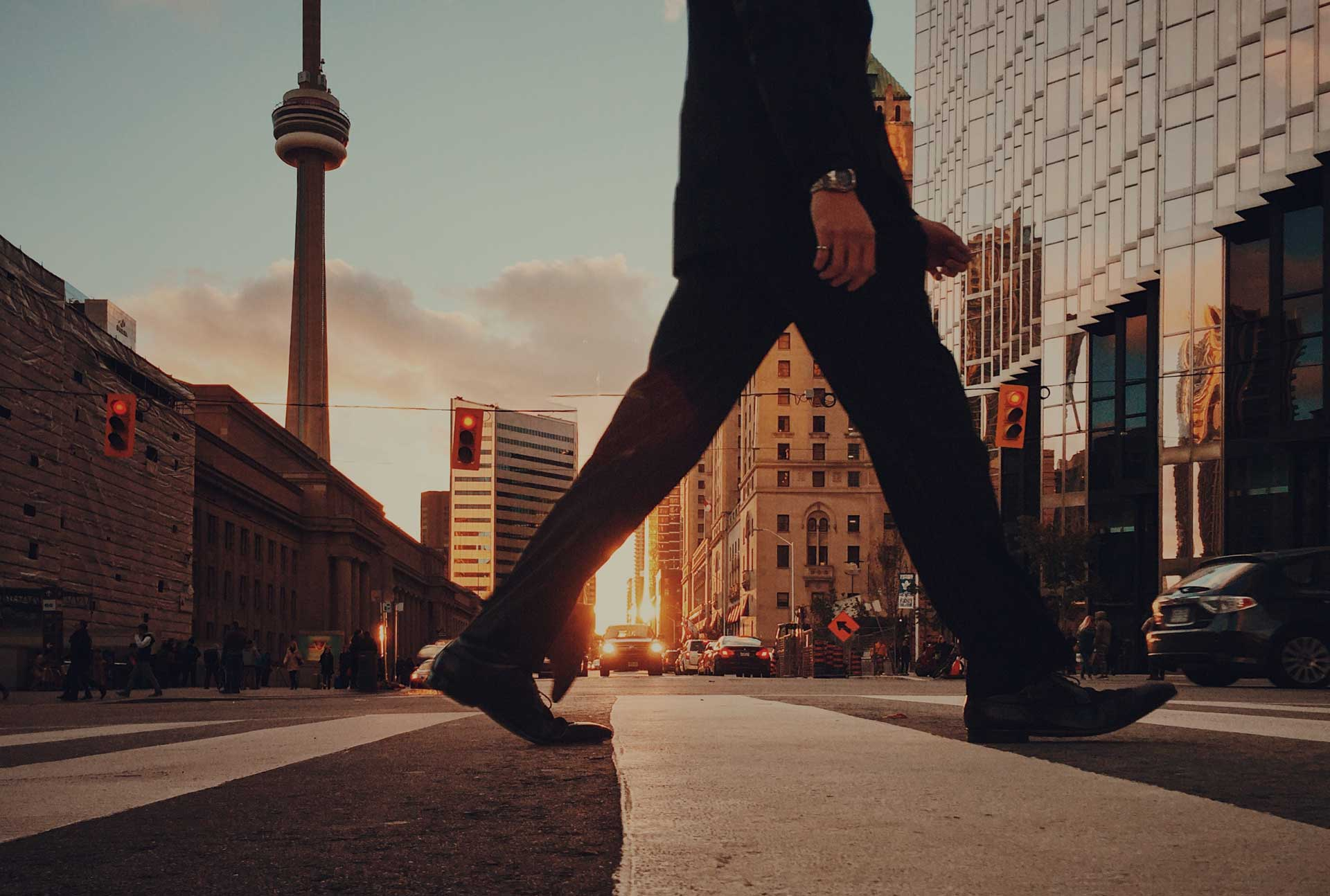 street level view of man in suit crossing road at sunset with toronto cn tower in the background