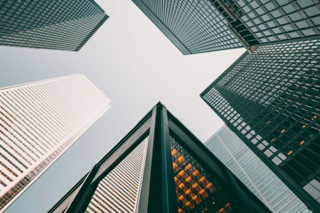 looking upwards at grouping of tall city office buildings