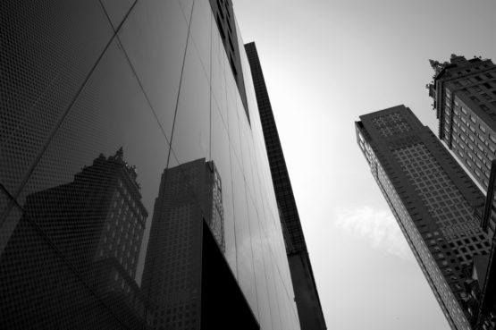 tall office building with buildings reflected on its glass panels